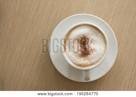 Top view of cappuccino coffee cup put on wooden table