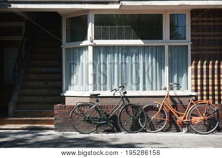 two dutch bicycles parked in front of residential building
