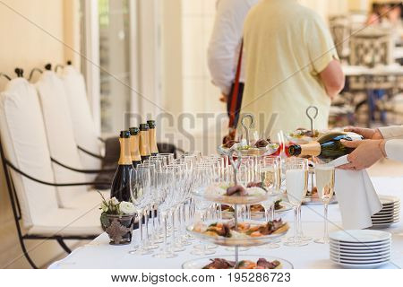Hands of the steward fills the glasses with champagne at the reception