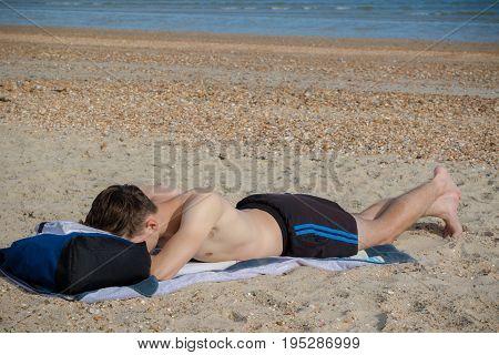 Teenage boy laying on a stoney beach