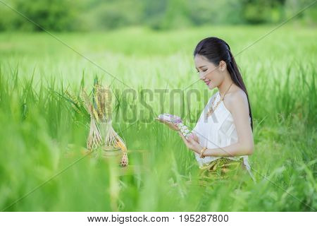 Thai farmer perform sacred rituals before planting.Thai traditional uniformwoman wearing typical thai dressidentity culture of ThailandHappy rural girl smiling in fieldportrait of asian woman