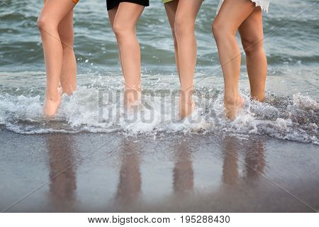 Pretty female legs on the background of the sea. Beautiful, perfect, cute, long and smooth woman's legs. Four adorable girls stand in a row.