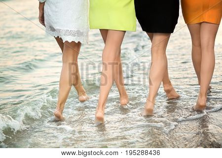 Long legs of women are walking on the sand of the beach. Sexy legs on the tropical sand beach. Walking female feet. Beautiful women enjoying her vacation on the beach.