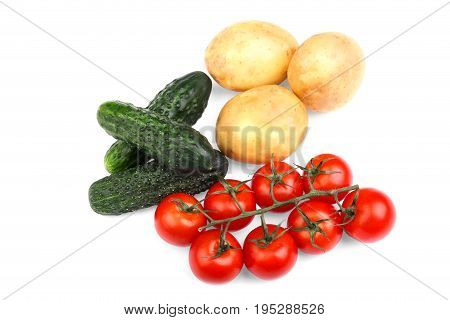 A few green cucumbers, bright tomatoes, and potatoes, isolated on a white background. Summer harvest of vegetables. Healthful traditional cuisine. Tasty, ripe, juicy, fresh and organic concept.