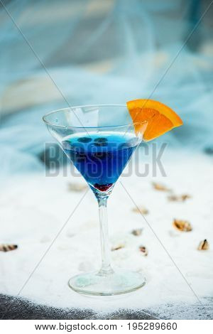 close up of blue cool refreshing summer cocktail drink with blueberryes on white sand with seashells background