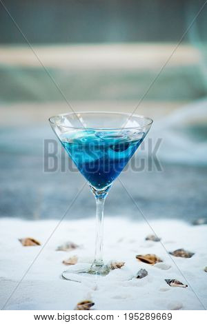 blue cool refreshing summer cocktail drink with ice  in glass on white sand with seashells background