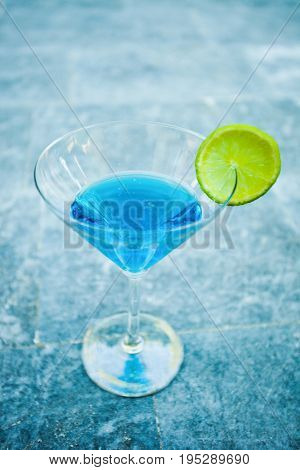 close up of  light blue  cool refreshing summer cocktail drink with lime slice on marble background outdoor
