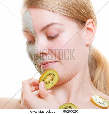 Woman Having Mud Mask On Face Holding Kiwi