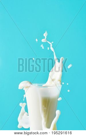 closeup of a glass of milk splashing everywhere on a blue background, with a negative space on top