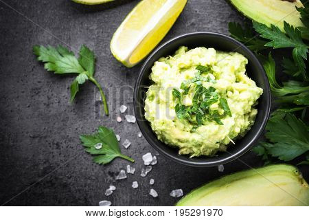 Traditional latinamerican mexican sauce guacamole in a bowl on black slate background. Top view copy space.