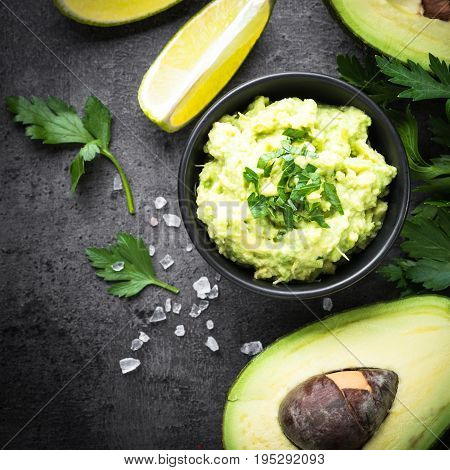 Traditional latinamerican mexican sauce guacamole in a bowl on dark slate background. Top view copy space. Square.