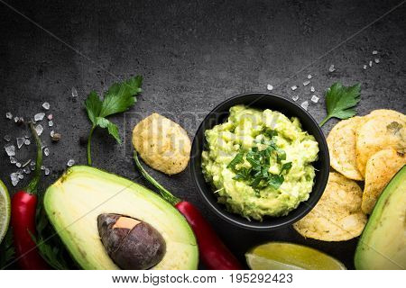 Traditional latinamerican mexican sauce guacamole chips and ingredients on black slate background. Top view copy space.