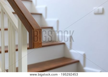 brown wood banister on staircase interior design of white modern house