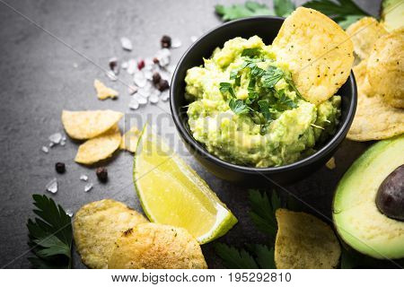 Traditional latinamerican mexican sauce guacamole chips and ingredients on black table.