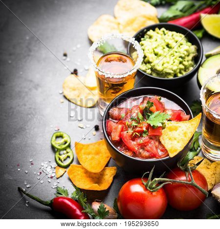 Latinamerican mexican food party sauce guacamole, salsa, chips and tequila on black.