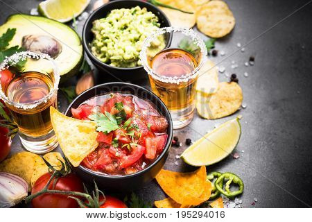 Mexican food party sauce guacamole, salsa, chips and tequila on black table.