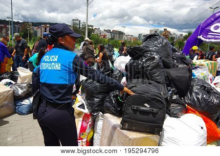 Quito, Ecuador - April, 17, 2016: Crowd of people looking the house destroyed by Earthquake, and heavy machinery cleaning the disaster in the city of Quito, Ecuador.