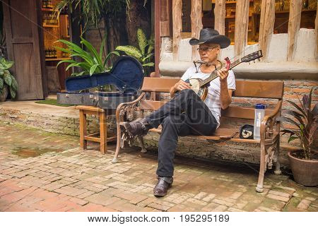Ratchaburi Thailand - June 10 2017: Senior man sitting on the bench in fron of his shop playing banjo to welcome the visitors in Suan Phueng of Ratchaburi Thailand
