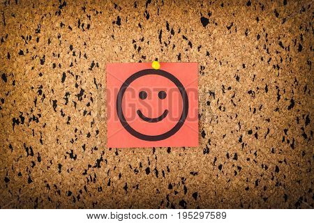 redpaper with smiling face on corkboard. bulletin board.