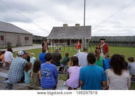 MACKINAW CITY, MICHIGAN / UNITED STATES - JUNE 18, 2017: Visitors listen to a lecture by costumed interpreters on the parade ground of Fort Michilimackinac, in the Colonial Michilimackinac State Park.