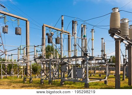 Summer. Electrical substation against the sky with clouds. In the frame insulators transformer wires. Ukraine. Kiev