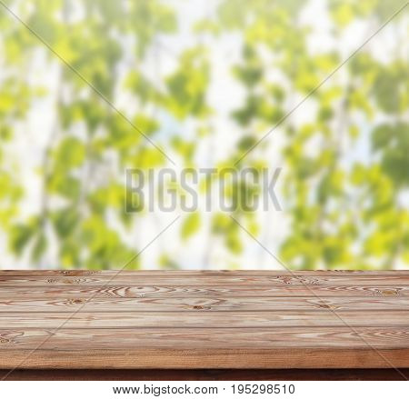 Wood table top on abstract blur background with birch branches - can be used for display or montage your products.
