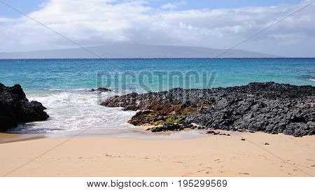 View of Private beach with sand and lava rocks in Maui Hawaii