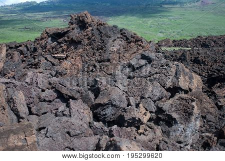 View of Black lava rocks line the shore at Keanae on the road to Hana in Maui, Hawaii