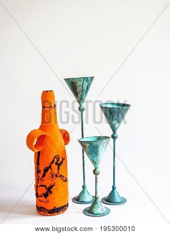 Three green metal candle holder and handcrafted orange paper mache bottle