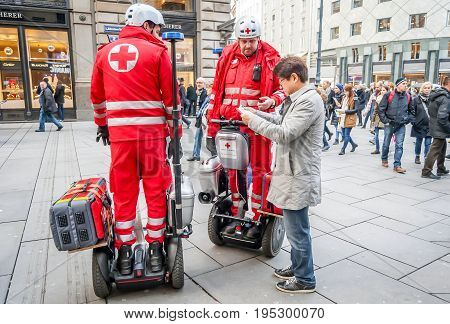 VIENNA, AUSTRIA. November 26, 2016. Vienna Red Cross (Wiener Rotes Kreuz) staff on segway PT give first medical assistance to those needed. The lost Japanese tourist asks them for directions.