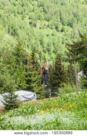 Romanian Adult Woman Wearing Casual Clothing On Zip-Line Canopy Experience In Retezat Mountains Romania