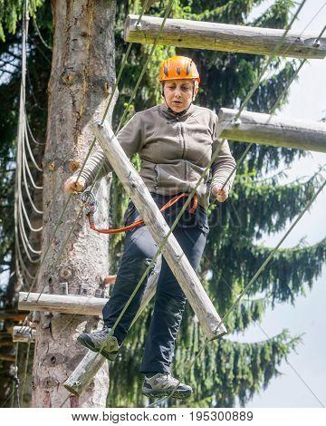 Tense Romanian Tourist Woman Enjoying Climbing Activity In Retezat Mountains Adventure Park On A Summer Day