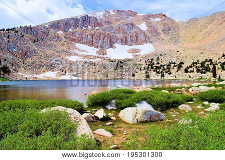 Alpine Lake surrounded by mountain peaks and tundra taken at Chicken Spring Lake in the Sierra Nevada Mountains, CA