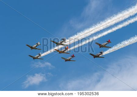 EDEN PRAIRIE MN - JULY 16 2016: Seven AT6 Texan airplanes fly overhead in cloudy sky with smoke trails at air show. The AT6 Texan was primarily used as trainer aircraft during and after World War II