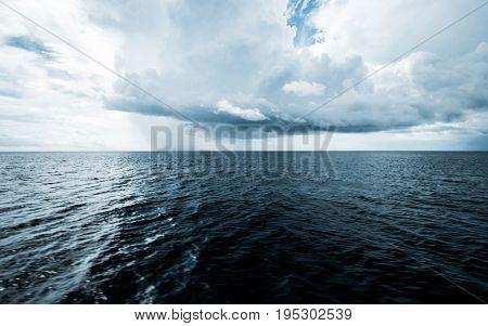 Dark clouds in open ocean. Tropical hurricane and sea storm