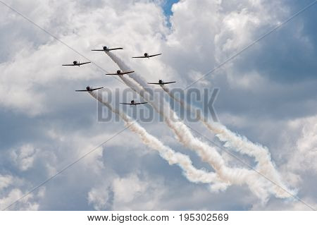 EDEN PRAIRIE MN - JULY 16 2016: AT6 Texan planes fly against cloudy sky in close formation at air show. The AT6 Texan was primarily used as trainer aircraft during and after World War II.