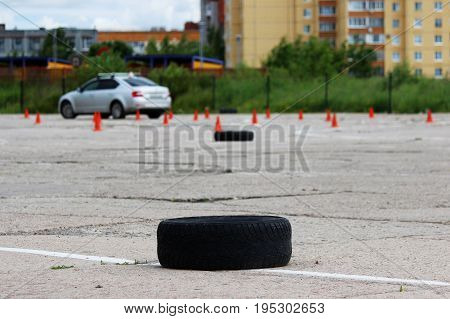 many plastic signaling traffic cones and Rubber tires from wheels are on site for training where drivers learn to ride on cars