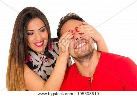 Close up of happy couple isolated on white background. Attractive man and woman being playful, woman putting her hands over his boyfriend eyes.