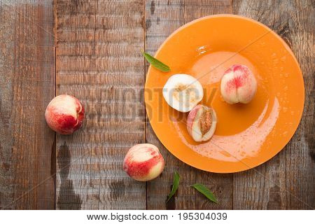 Still life of fresh peaches. Peaches are scattered on the table.