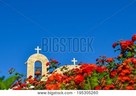 Orthodox church with a tiled roof and a bell. Red roses in the foreground. Cyprus. Ayianapa. Church of St. Epiphany.