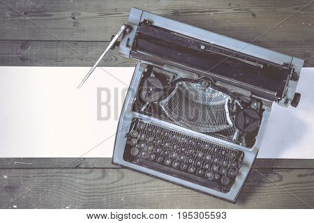 An old typewriter with paper stands on a wooden table.Stylized retro photo.