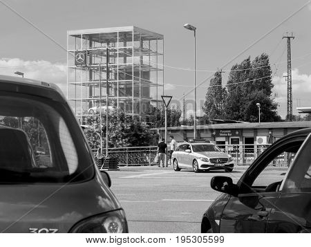 KEHL GERMANY - JUL 14 2017: Black and white photo of German Police in Mercedes wagon car surveying the traffic on busy German street with glass cube with multiple Mercedes-Benz luxury cars inside