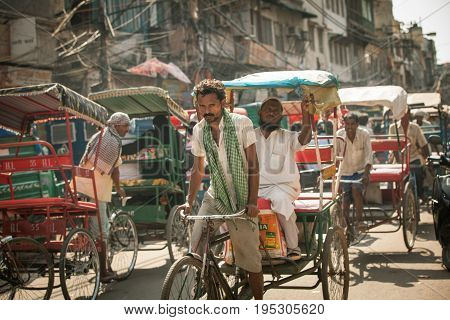 DELHI INDIA - SEPTEMBER 18: Cycle rickshaw riding the vehicle under the heat on the street of Old Delhi India on September 18 2014.