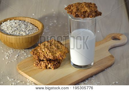 Fresh oatmeal cookies with milk Wooden plate with oatmeal