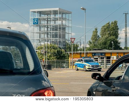 KEHL GERMANY - JUL 14 2017: German Police in Mercedes wagon car surveying the traffic on busy German street with glass cube with multiple Mercedes-Benz luxury cars inside