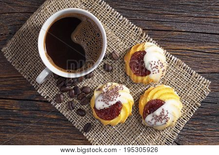 Cup of hot coffee and cookies with jam and sugar icing for breakfast on rustic wooden table top view