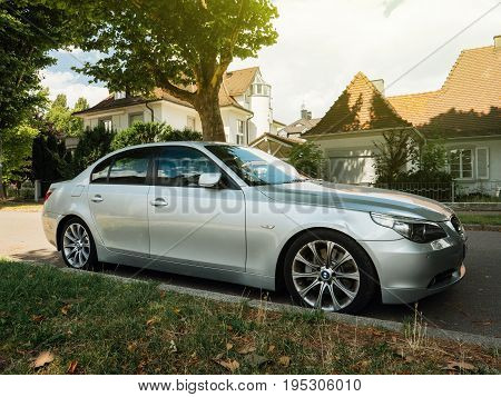 KEHL GERMANY - JUL 14 2017: Silver BMW luxury limousine sedan parked in city with luxury real estate building in the background beautiful german house