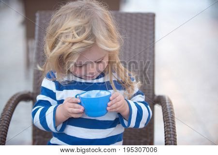boy little child with white mustache on cute face and blond long hair in striped shirt sitting in brown armchair holding blue cup with tasty domestic milk