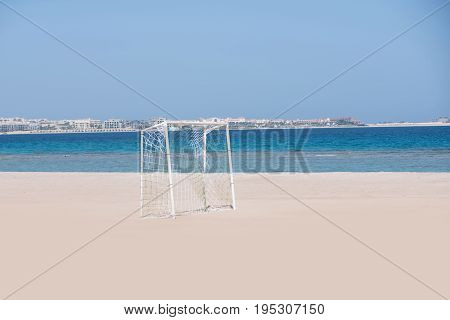 Goal post for training soccer sport with white net standing on sand beach on natural background of blue ocean and sky horizon in summer