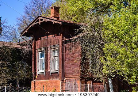 Old wooden house near a green tree on a sunny day. Russia